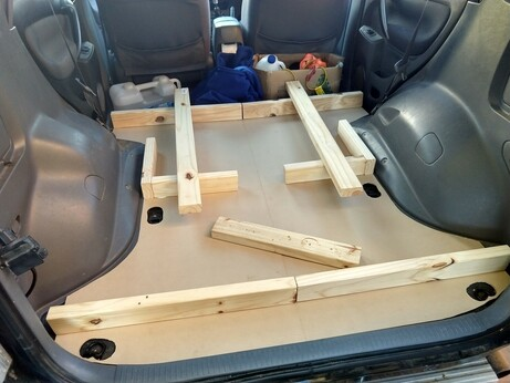 Some MDF boards laid flat in the back of a RAV4, with some pine pieces starting to define some squared off areas on top