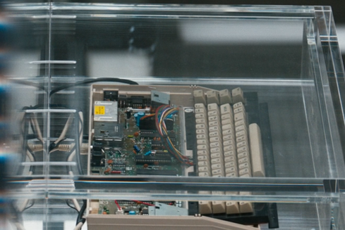 A Commodore 64 with the upper case removed and the keyboard pulled forward and mounted flat in front of the motherboard, inside a clear perspex drawer.