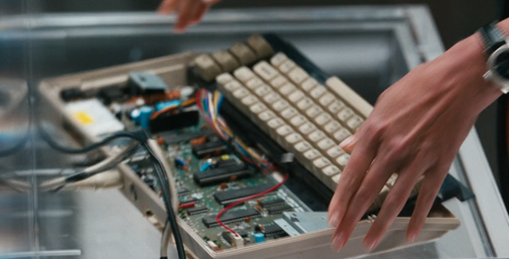 A Commodore 64 with the upper case removed and the keyboard pulled forward and mounted flat in front of the motherboard, being held up in someone's hands on an angle showing the motherboard clearly